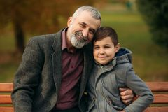 Grandpa and his grandson spend time together in the park. They are sitting on the bench. Walking in the park and. Rejoicing Royalty Free Stock Images