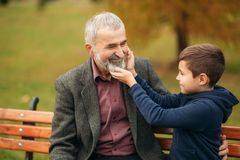 Grandpa and his grandson spend time together in the park. They are sitting on the bench. Walking in the park and. Rejoicing royalty free stock photos