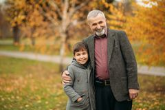 Grandpa and his grandson are walking in the park. The spend time together.  royalty free stock photos
