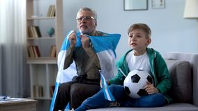 Grandpa holding Argentina flag, watching football with boy, worrying about game. Stock photo stock photography