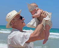 Grandpa is holding a little granddaughter. Happy grandpa is holding a little granddaughter. Background - the sea Royalty Free Stock Photo