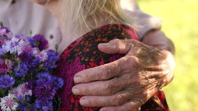Grandpa hugging his wife, wrinkled hand close-up. stock video