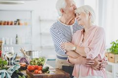 Grandpa hugs and kisses smiling grandma. During cooking healthy meal in kitchen royalty free stock image