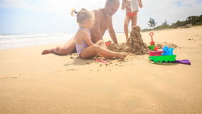 Grandpa Kids Build Sand Castle on Beach by Wave Surf stock video
