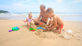 Grandpa Kids Build Sand Castle on Beach by Wave Surf stock video footage