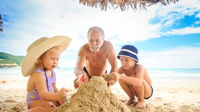 Grandpa Little Girl Boy Make Sand Heap on Beach by Surf stock video footage