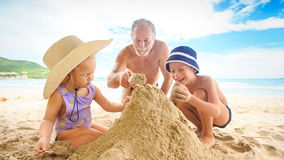 Grandpa Little Girl Boy Spread on Sand Heap on Beach by Surf stock footage