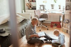 Grandpa looks photo album with his wedding, little boy using electronic tablet. Different generations stock images