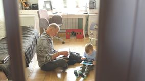 Grandpa looks photo album with his wedding, little boy using electronic tablet