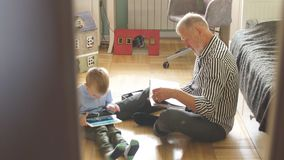 Grandpa looks photo album with his wedding, little boy using electronic tablet.  stock footage