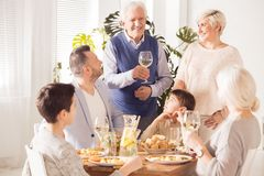 Grandpa making a speech. Happy grandpa making a speech at a celebration dinner royalty free stock photo