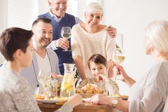 Grandpa making a toast. At a happy family dinner royalty free stock images