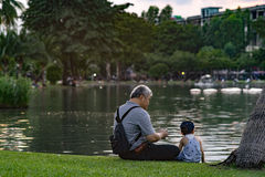Grandpa and nephew relaxing in chatuchak park Stock Photos