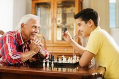 Grandpa Playing Chess Board Game With Grandson At Home. Happy little kid playing chess with senior men at home. Family relationship with grandfather and grandson stock photo