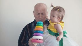 Grandpa plays with her granddaughter, collects a multi-colored pyramid