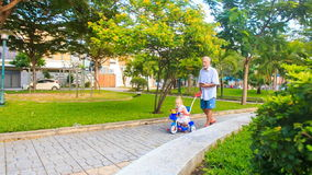 Grandpa Pushes Tricycle with Little Girl Reads Smartphone in Park. Bearded grandfather pushes child's tricycle with little blond girl along park path reads
