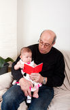 Grandpa reading red book to baby girl. Happy grandfather reading a little red book to a baby girl. Infant sitting on fathers lap while being educated reading stock images