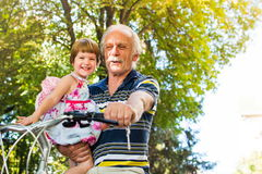 Grandpa riding bicycle with granddaughter in hands. Grandpa riding bicycle with granddaughter in his hands stock photos