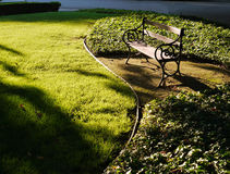 Grandpa's bench. A wrought iron and wood bench in a park like setting, green grass and ivy  glowing in late afternoon sun Royalty Free Stock Image