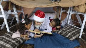 Grandpa in santa hat reading a book with kids stock footage