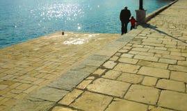 Sea wall, Corfu, Greece. Family walking along sea wall in Garitsa district of Corfu, Greece Royalty Free Stock Photography