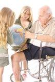 Grandpa showing grandchildren the globe upclose Stock Photo