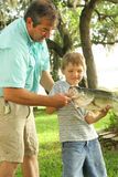 Grandpa showing how to hold a fish Stock Image