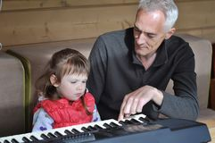 Grandpa teaches little girl to play piano. Concept of music study and creative hobby Royalty Free Stock Photos