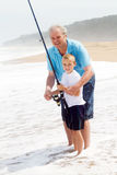 Grandpa teaching grandson fishing stock photos