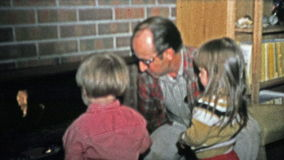 1973: Grandpa teaching the kids about fireplace safety. stock video