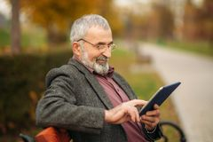 Grandpa uses a tablet sitting in the park on the bench royalty free stock photos