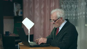 Grandpa uses a laptop at home. stock video footage