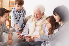Grandpa using tablet. Grandchildren teaching grandpa how to use tablet royalty free stock images