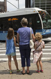 Grandparent with children wait to cross street Stock Image