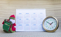 Grandparent Frost with calendar and hour. Grandparent Frost with paper calendar and round hour on beige background Royalty Free Stock Photography