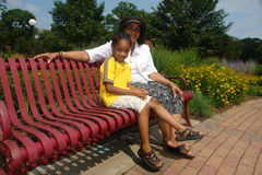 Grandparent and grandchild. A picture of a grandparent and child sitting on bench in garden Royalty Free Stock Photography