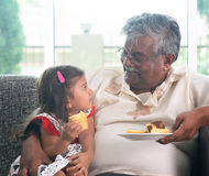 Grandparent and grandchild eating cake Royalty Free Stock Photos