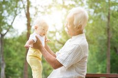 Grandparent and grandchild. Senior old men with baby grandchild, Asian family, life insurance concept stock photos