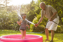 Grandparent and grandkid playing with hose Stock Images