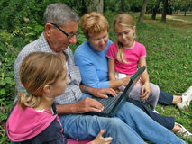 Grandparent, twins grandchild with laptop. View at a happy - smiling grandparent (grandmother, grandfather) and grandchild sitting with laptop on green grass in royalty free stock photography