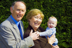 Grandparents. Smiling grandparents holding happy baby boy portrait Royalty Free Stock Photos