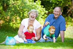 Grandparents. Happy handsome grandparents with twin grandsons outdoor portrait Royalty Free Stock Image