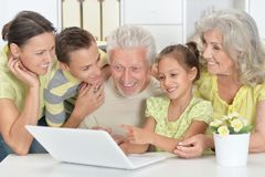 Grandparents with adult daughter and grandchildren together. Grandparents with adult daughter and grandchildren using laptop together at home stock photo