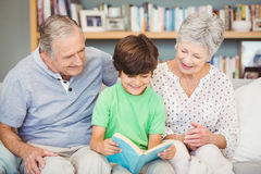 Grandparents assisting grandson while reading book Stock Photography