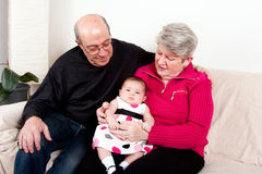 Grandparents with baby girl. Grandparents holding baby girl on lap while sitting on couch in living room as a happy family royalty free stock image