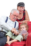 Grandparents babysitting their granddaughter. Sitting together ion a couch pointing out information on the tablet computer to her as they enjoy an e-book stock images