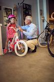 Grandparents buying new bicycle and helmets for little girl. Happy grandparents buying new bicycle and helmets for little girl stock photos