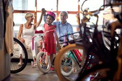 Grandparents buying new bicycle for little girl. Happy grandparents buying new bicycle for little girl stock image