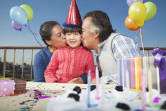 Grandparents celebrating birthday of granddaughter Stock Photos