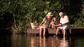 Grandparents and child near river. Elderly people sitting near water with granddaughter. Grandfather tutoring grandchild with book on nature background stock video